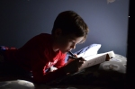 A photo of a boy reading and drawing in bed